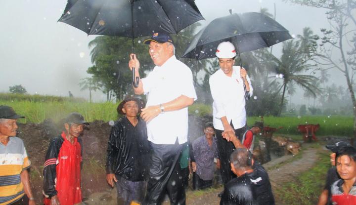 Foto Berita Hujan-hujan, Jokowi Tinjau Irigasi Kecil di Tanah Datar