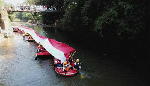 Foto Askrindo-Yalisa Bentangkan Merah Putih di Sungai Ciliwung