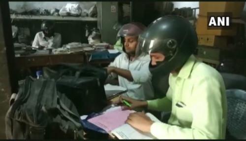 Foto Viral Pegawai Pemerintah di India Pakai Helm saat Bekerja, Katanya untuk...